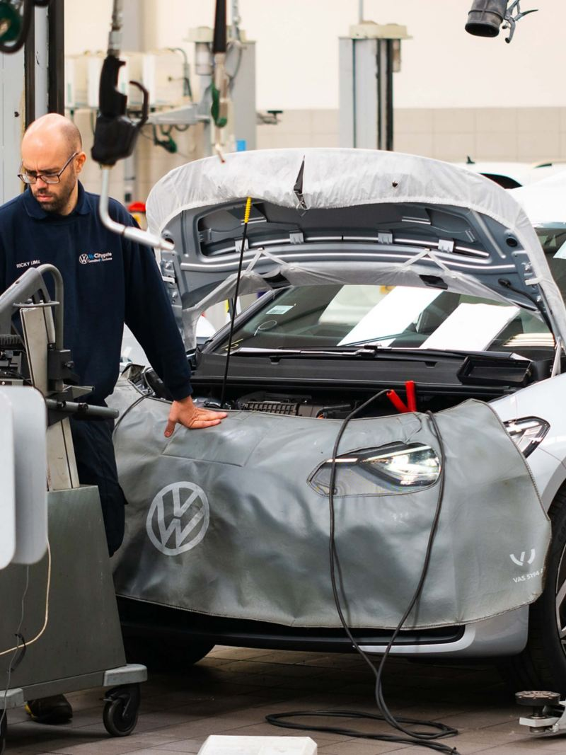 A technician standing in front of a VW with the bonnet raised and jump leads plugged in