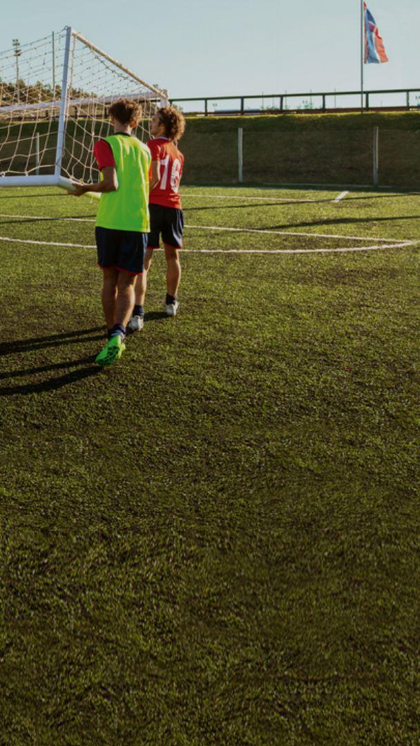 Cinq jeunes joueurs de soccer en maillot rouge portent un filet de soccer pour le déposer à sa place.