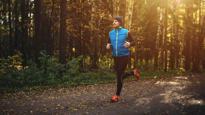 A man in a blue vest and toque goes for a jog in the forest at dawn.