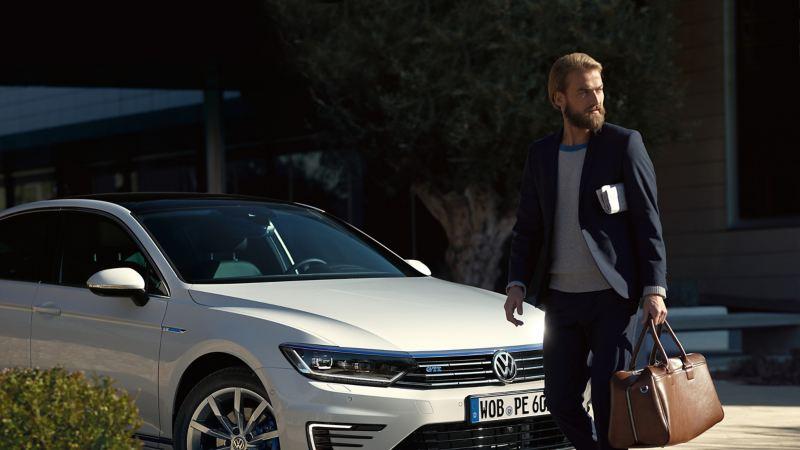 Uomo elegante che passeggia davanti alla Volkswagen Passat GTE per uso aziendale
