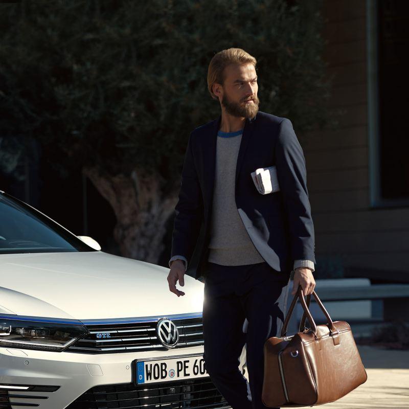 Un uomo con abito elegante e borsa da lavoro passa davanti alla sua Volkswagen Passat GTE per uso aziendale