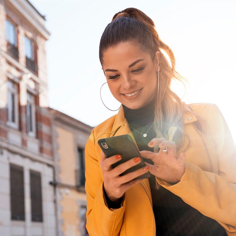 Eine Frau steht vor einem Haus und schaut auf ihr Smartphone