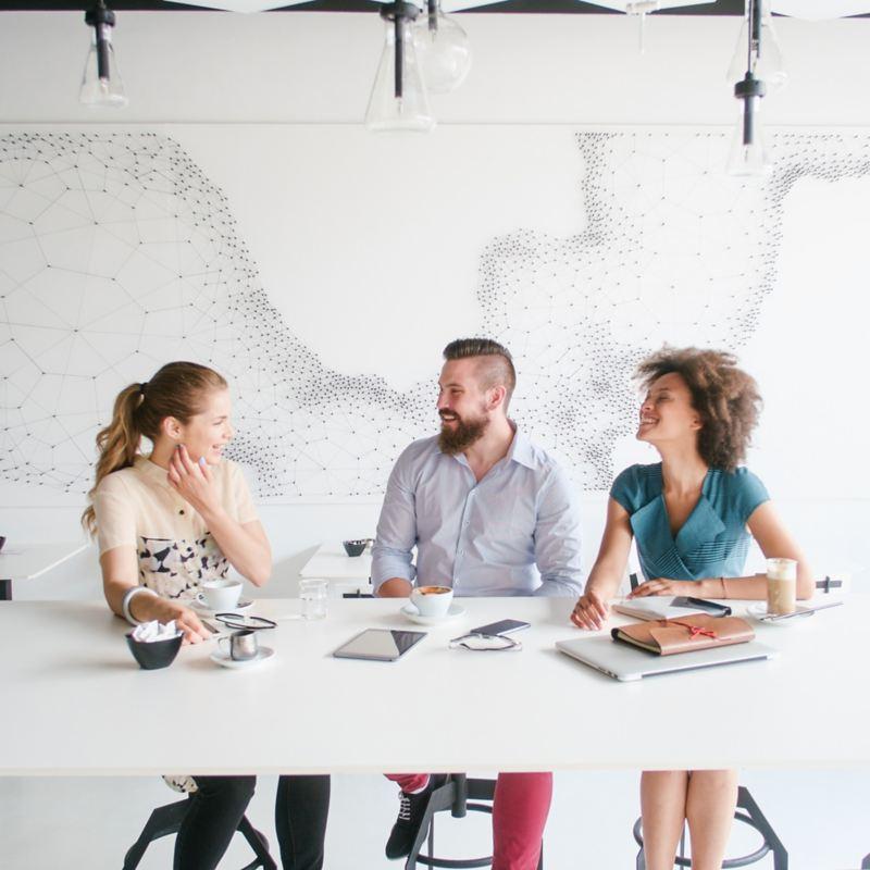 Drei junge Erwachsene sitzen an einem Tisch und unterhalten sich