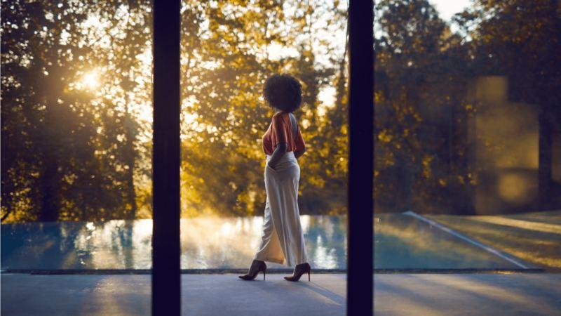 Une femme marche à côté d'une piscine extérieure