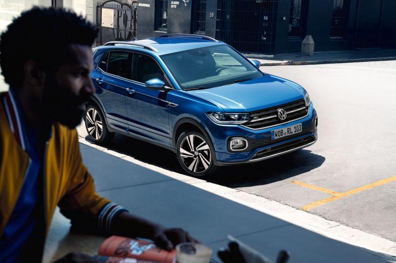 VW T-Cross staat op straat in de stad, deels in de schaduw, op de voorgrond wandelt een man