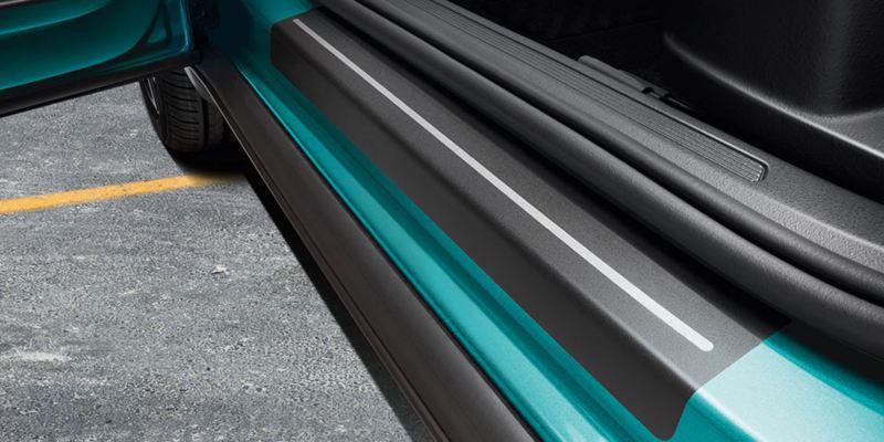 Dettaglio delle pellicole battitacco nere con strisce argento originali Volkswagen, applicate su una T-Cross.