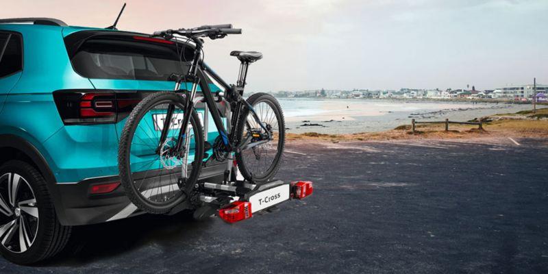 """Dettaglio del porta biciclette pieghevole """"Compact"""" originale Volkswagen, montato sul retro di una T-Cross. Disponibile per due o tre biciclette."""