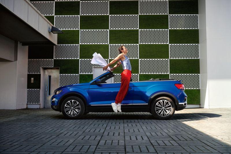 Μια γυναίκα δίπλα από το volkswagen T-Roc Cabriolet