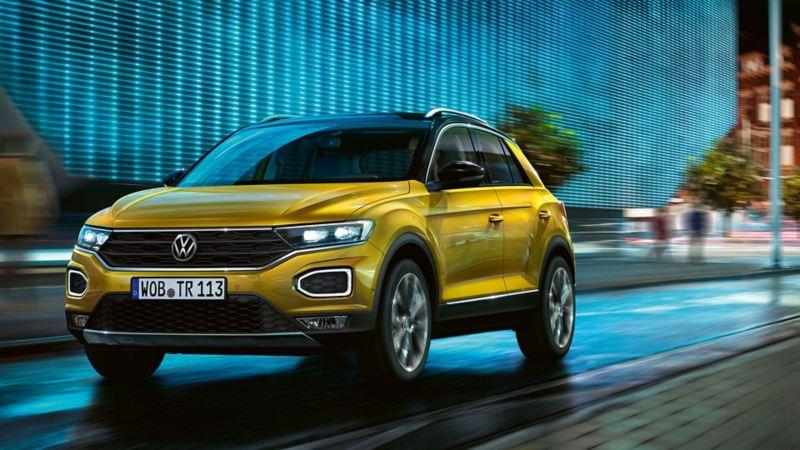 Ein gelber VW T- Roc fährt durch die Stadt.