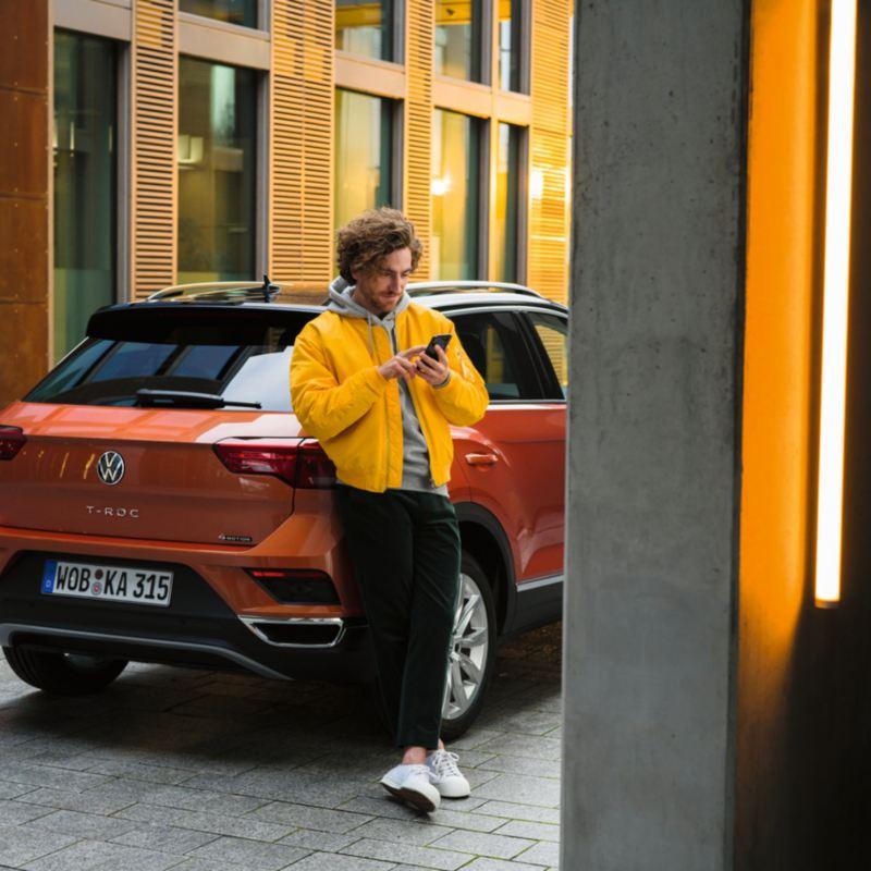 Un uomo consulta il suo smartphone appoggiato alla fiancata di una Volkswagen T-Roc, vista 3/4 posteriormente.