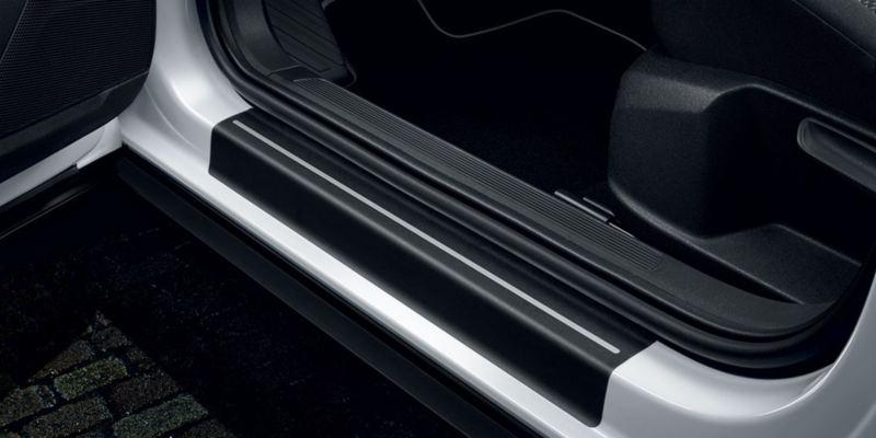 Dettaglio delle pellicole battitacco nere con strisce argento originali Volkswagen, applicate su una T-Roc.