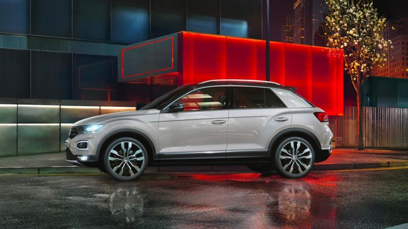 Vista laterale di Volkswagen T-Roc parcheggiata davanti a un edificio moderno.