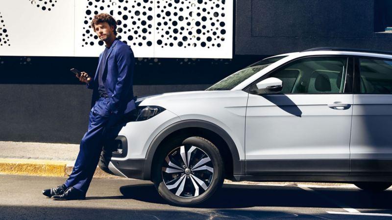 Um homem de fato está encostado ao seu SUV Volkswagen.