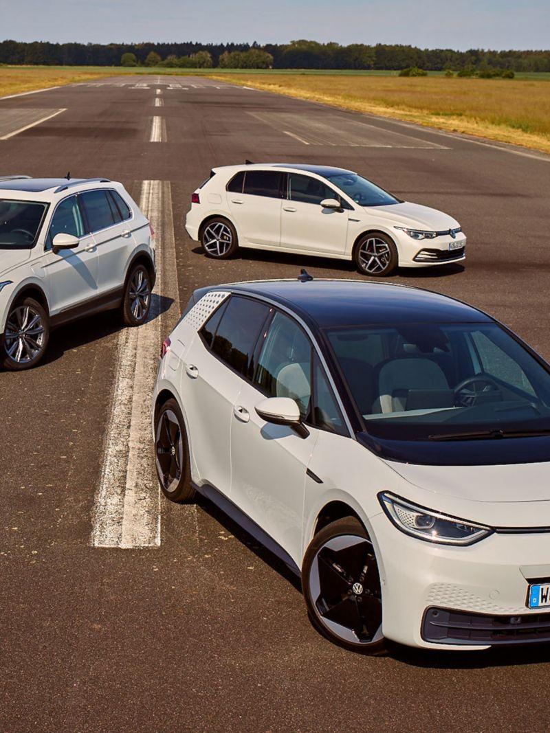 VW ID.3, Tiguan eHybrid et Golf GTE en blanc garés sur une piste d'atterrissage devant un champ, avant visible