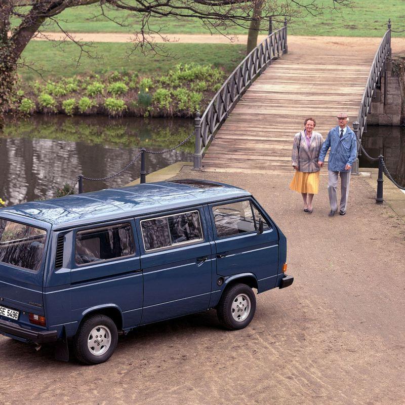A Multivan num parque ao pé de um lago. Um casal mais velho passeia ao lado dela.