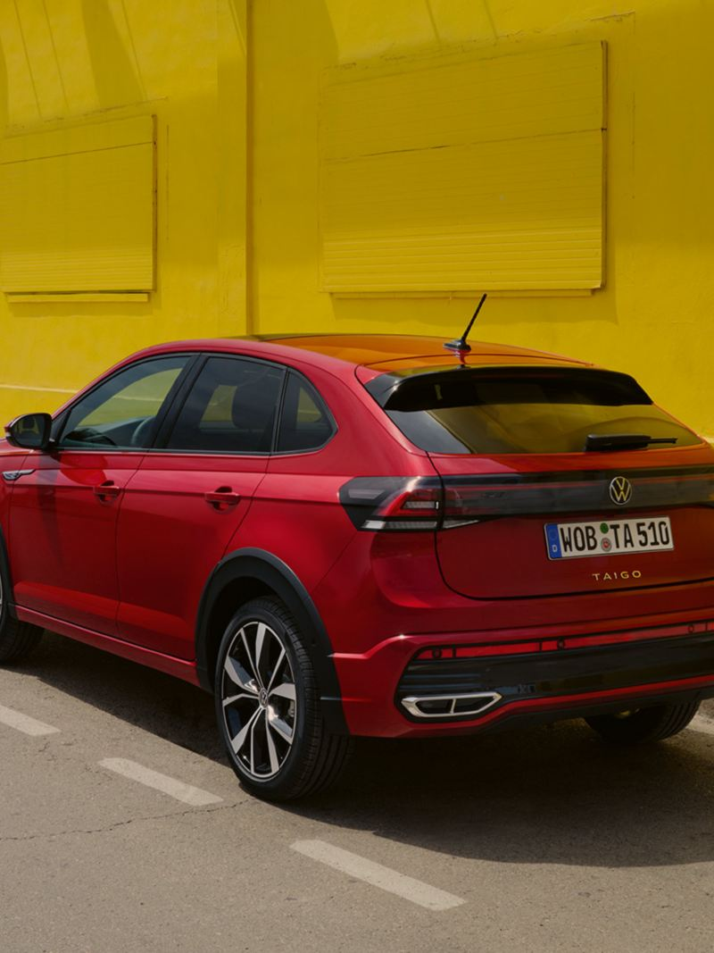 VW Taigo in red on the roadside in front of a yellow building, rear and side view, woman is walking towards the vehicle