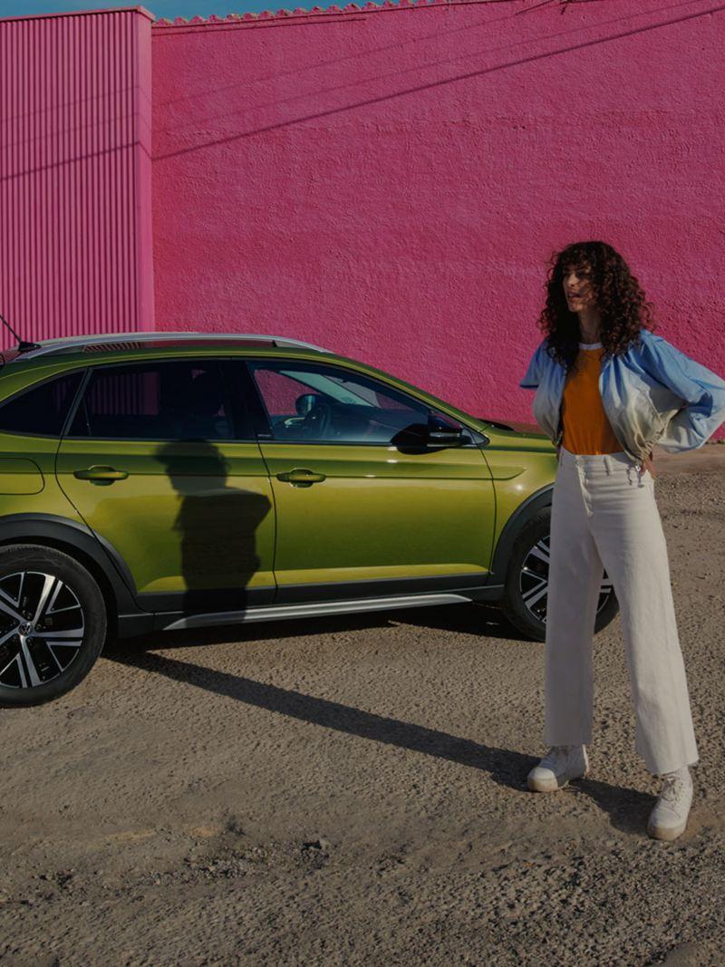 Volkswagen Nouveau Taigo vert avec une femme debout devant