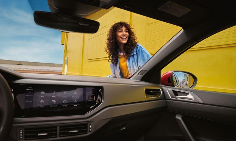 Interni della Volkswagen Taigo R-Line: vista del cruscotto e di una donna attraverso il parabrezza