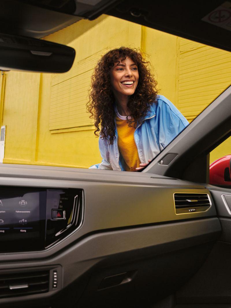 Vue de l'intérieur du Volkswagen Nouveau Taigo rouge avec une femme à travers le pare brise