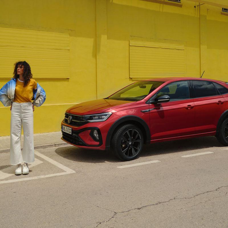 Una ragazza si allontana da una Volkswagen Taigo parcheggiata a bordo strada, vista lateralmente.
