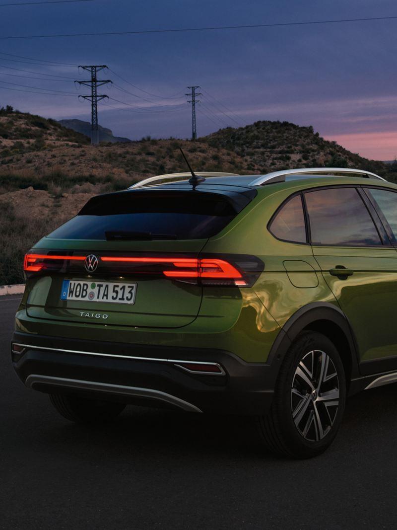 Volkswagen Nouveau Taigo vert avec un homme debout devant dans la pénombre