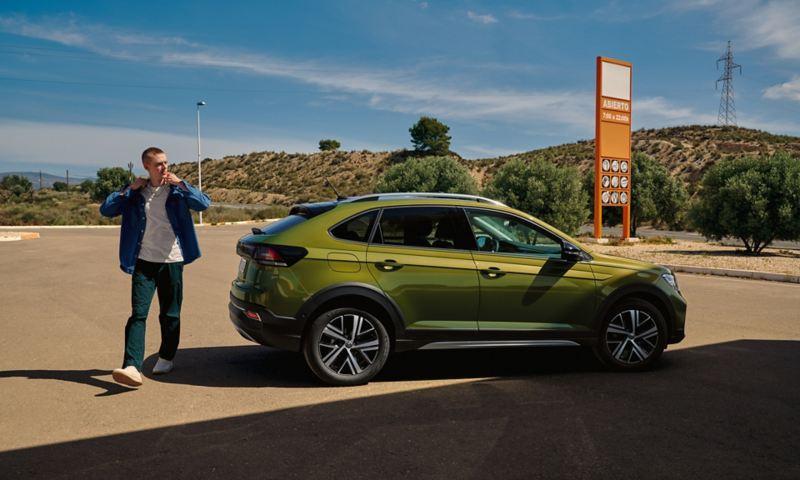 Un VW Taigo vert sur un parking, vue latérale, un homme passe devant le véhicule
