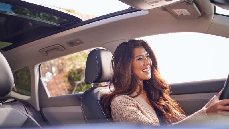 Une femme au volant d'un véhicule Volkswagen avec toit ouvrant