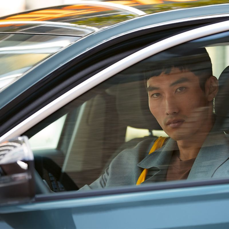 A man in a driver's seat looking out of the window