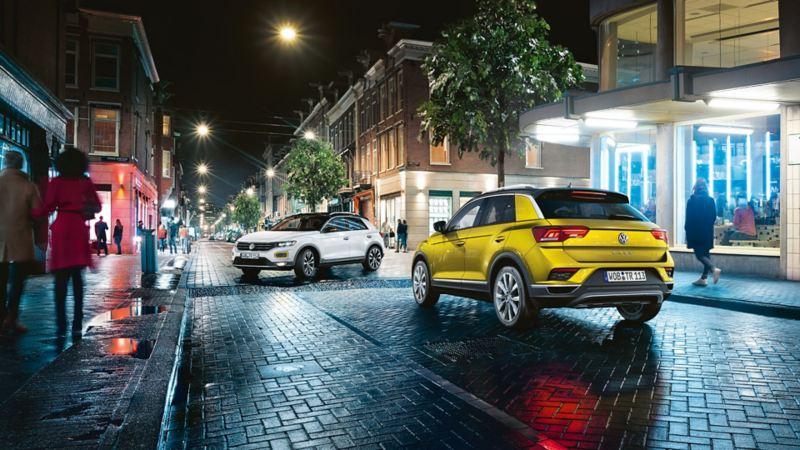 Les T-Roc Sport et T-Roc Style en ville, de nuit à un carrefour en T