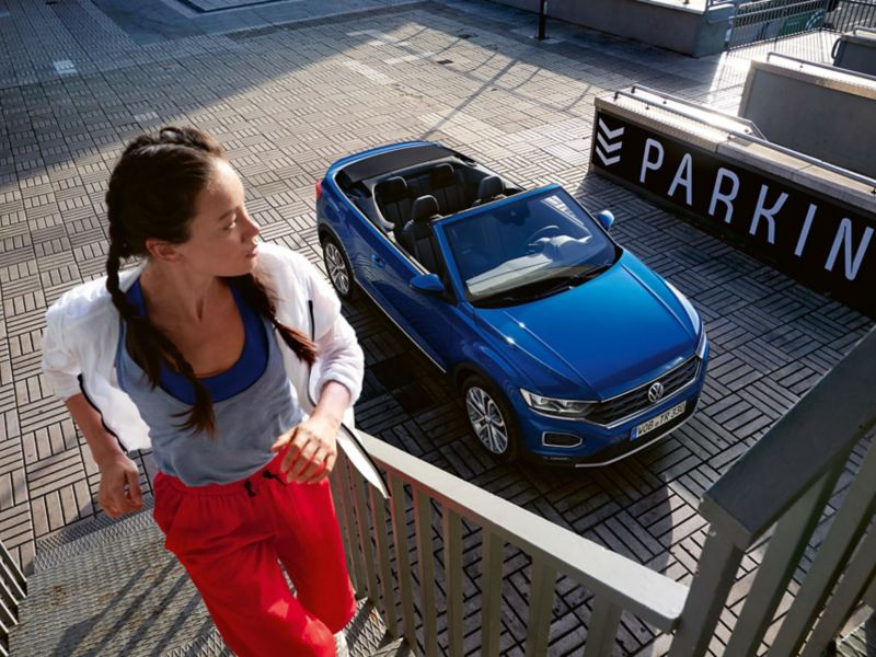 Μια γυναίκα ανεβαίνει τρέχοντας μια σκάλα, το volkswagen T-Roc Cabriolet παρκάρει στο φόντο