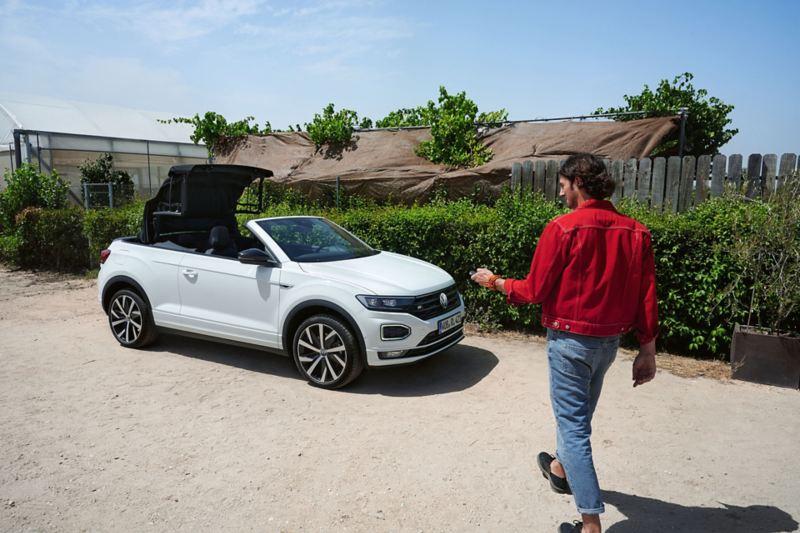 Un homme ouvre le toit souple du VW T-Roc Cabriolet