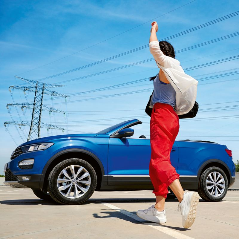 Μια γυναίκα κινείται πίσω από ένα volkswagen T-Roc Cabriolet