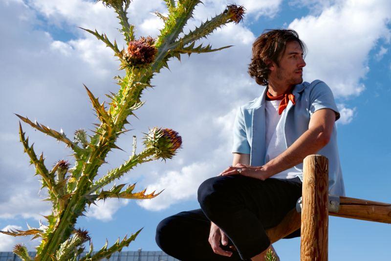 Un homme assis sur une cloture en bois