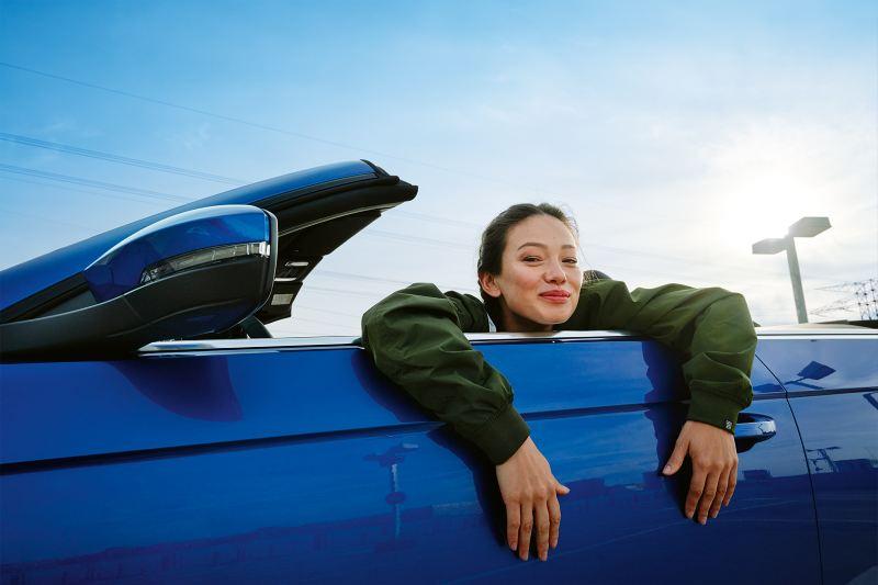 Μια γυναίκα βρίσκεται μέσα στο volkswagen T-Roc Cabriolet και γελά