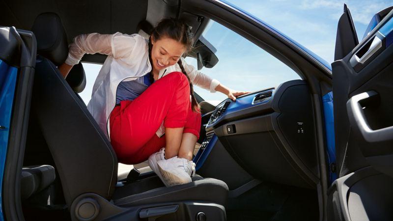 Un ragazza sale con un salto al posto di guida della sua auto Volkswagen.