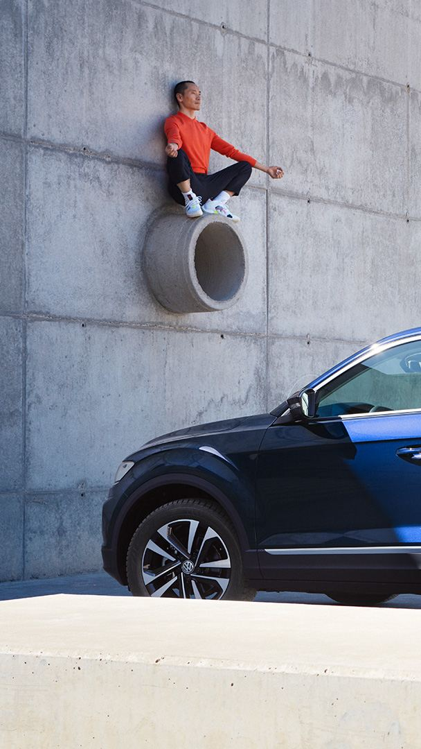 3/4 vista posteriore della VW T-Roc UNITED davanti a un muro di cemento, uomo seduto su un tubo