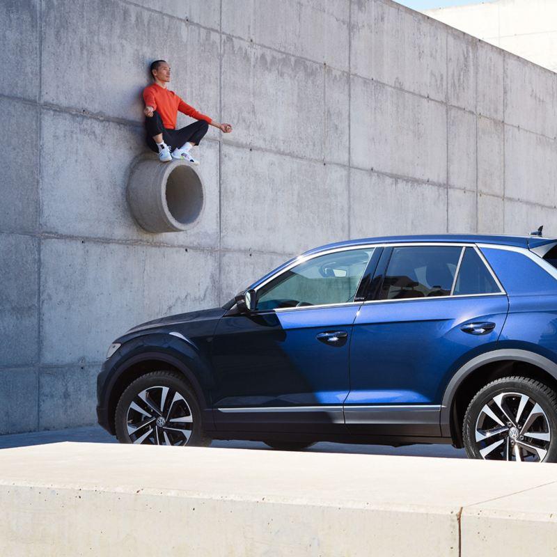 3/4-Rückansicht des VW T-Roc UNITED vor einer Betonwand, Mann sitzt auf einem Rohr.
