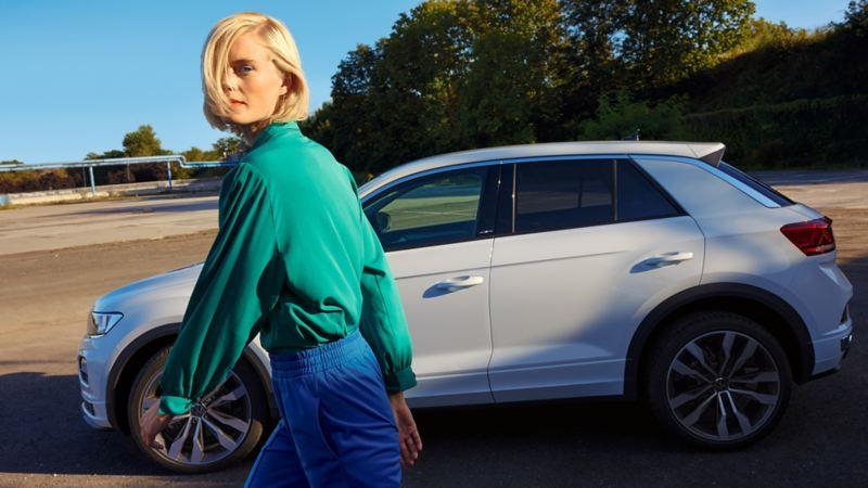 Une VW T-Roc ACTIVE blanche sur un parking en ville. Vue de profil. Une femme passe devant.
