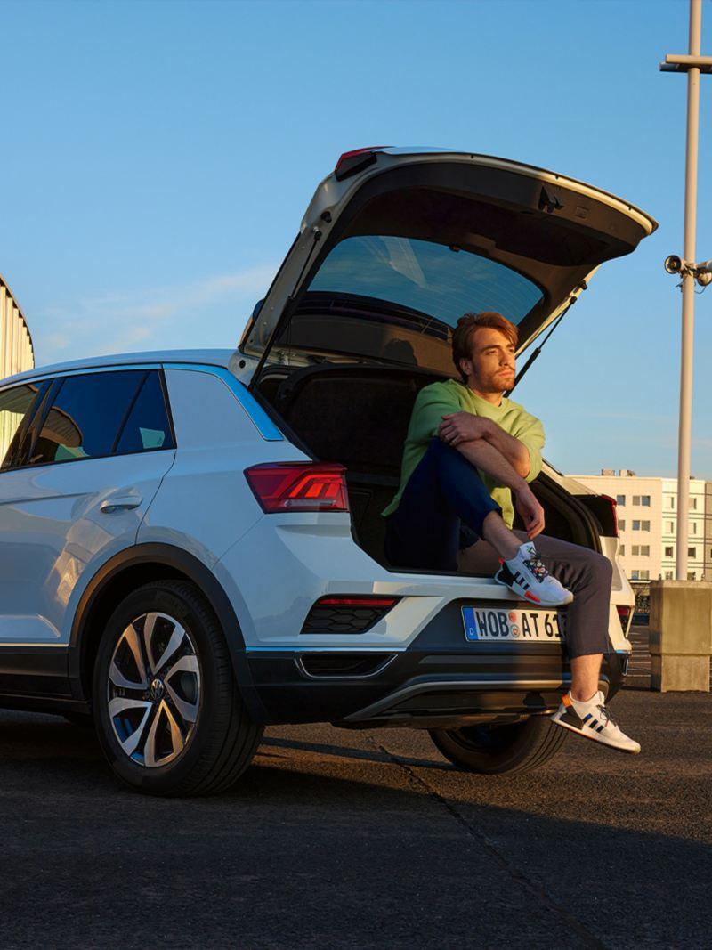 VW T-Roc ACTIVE blanche garée dans un environnement urbain avec un compartiment à bagages ouvert.