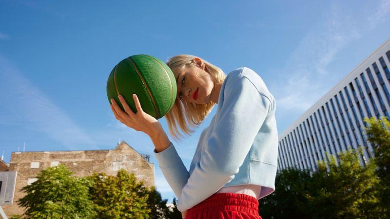 Femme tenant un ballon de basket dans un environnement urbain avec un ciel bleu en arrière-plan.