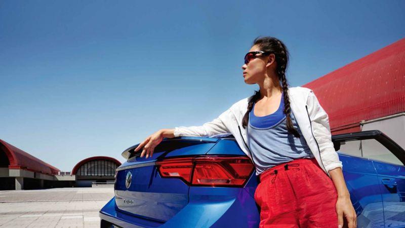 Una donna appoggiata alla sua cabriolet Volkswagen, vista posteriormente.