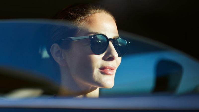 Frau mit Sonnenbrille sitzt bei heruntergelassener Scheibe in einem VW.