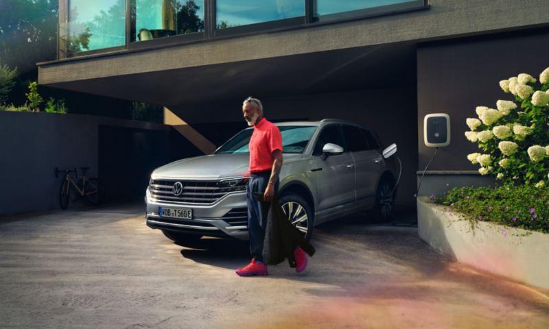 Volkswagen Touareg eHybrid couleur argent, vue de face, se charge dans l'allée, alors qu'un homme passe devant