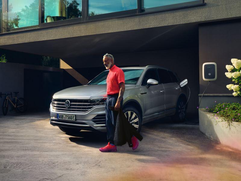 Volkswagen Touareg eHybrid en argent, vue avant-latérale, charge dans l'entrée, un homme passe