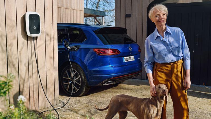 Una donna in piedi con il suo cane davanti ad una Volkswagen Touareg eHYBRID, vista posteriormente, in carica presso una wallbox.