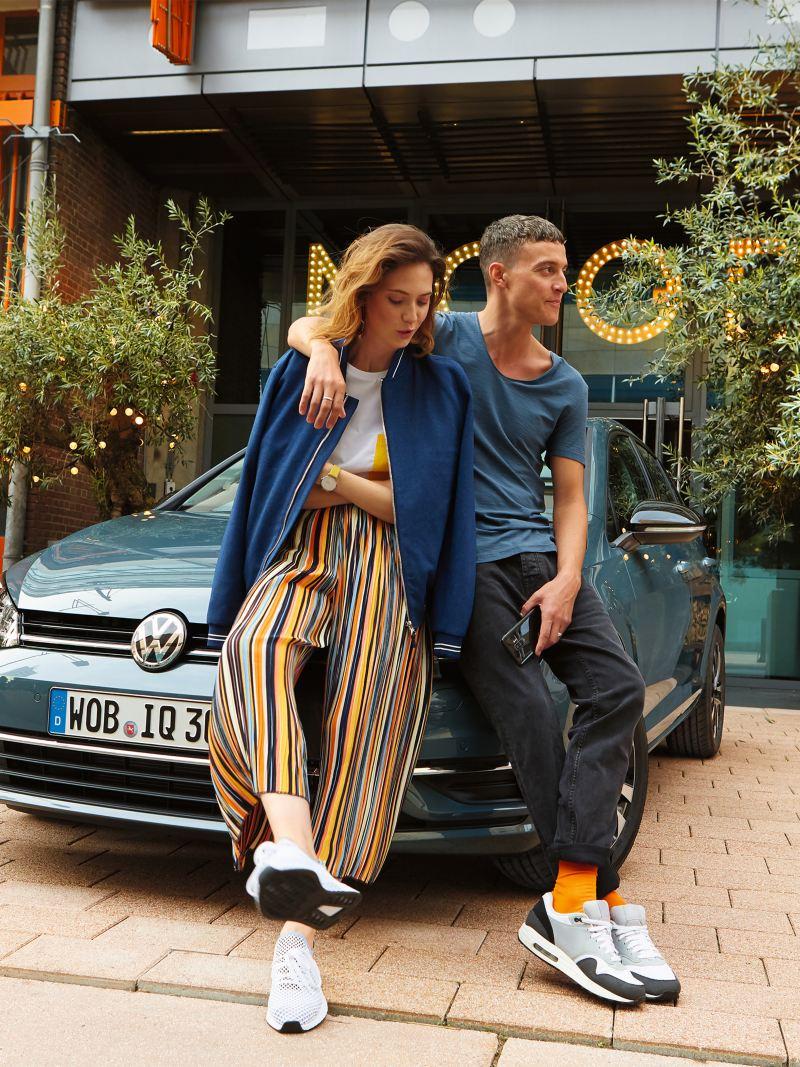 Una coppia posa davanti a una Volkswagen Polo, parcheggiata in città.