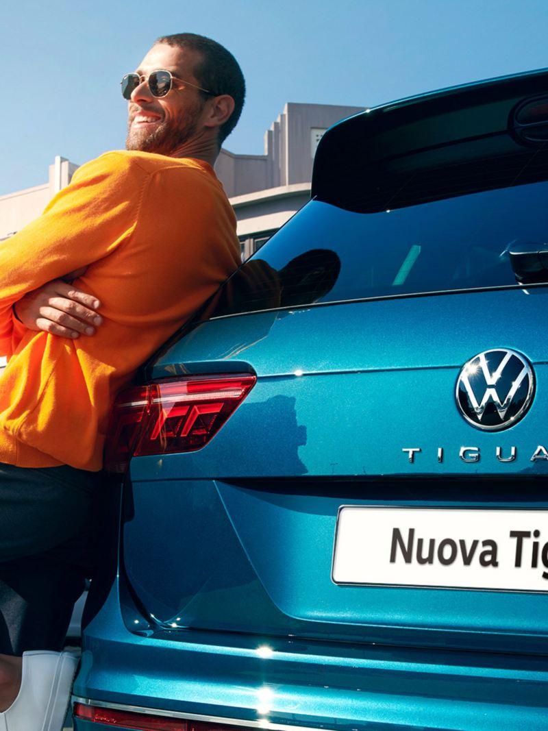 Un uomo con gli occhiali da sole si appoggia a Volkswagen Nuova Tiguan.