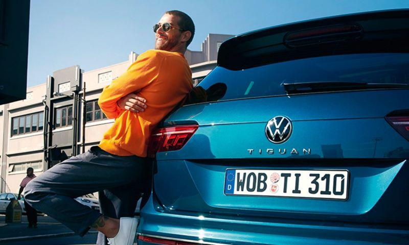 Päikeseprillidega mees toetub vastu VW Tiguani tagaosa