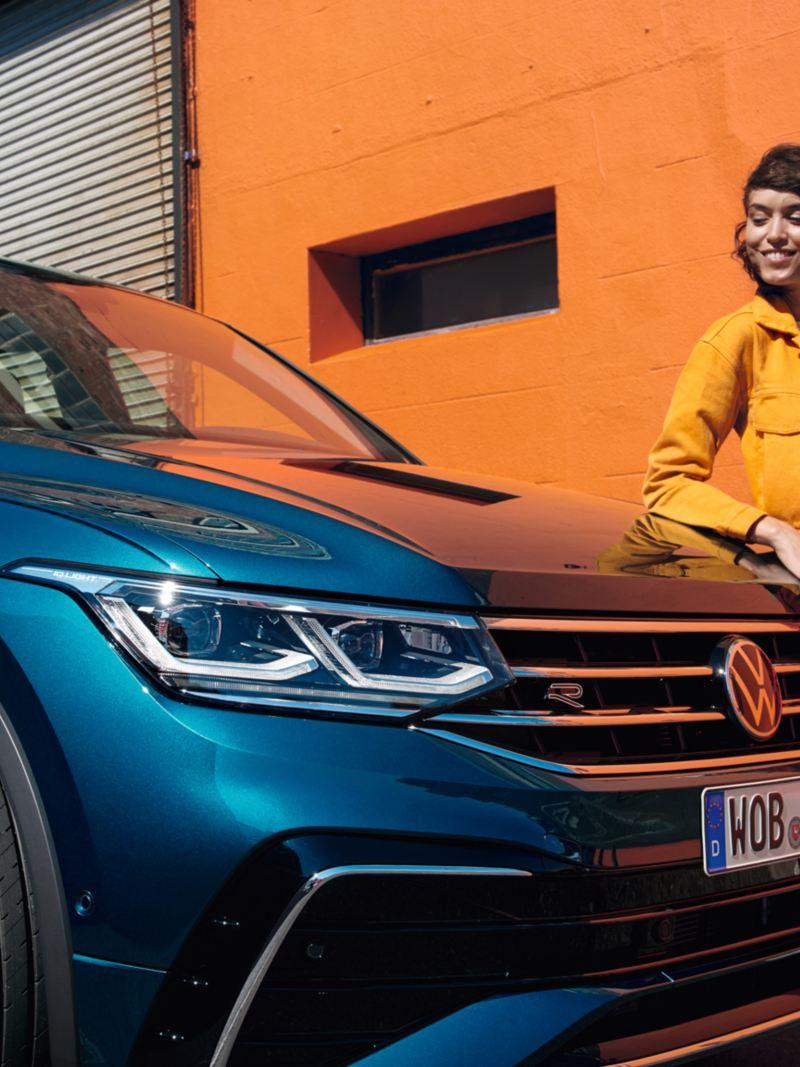 Femme appuyée contre le capot du VW Tiguan avec un sourire