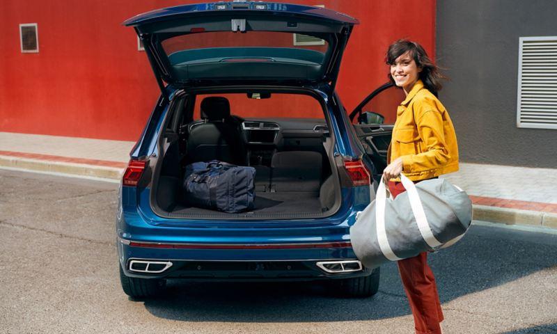 Spordikotiga naine VW Tiguani avatud tagaluugi juures